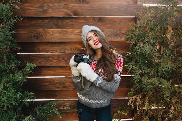Hübsches mädchen mit langen haaren und schneeweißem lächeln in strickmütze und handschuhen auf holz im freien. sie trägt einen pullover, hält die kamera und lächelt.