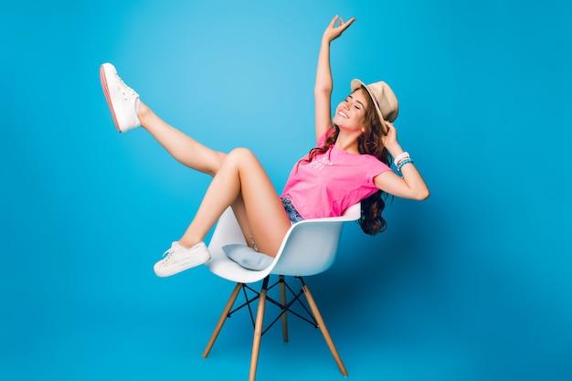 Hübsches mädchen mit langen lockigen haaren im hut kühlt im stuhl auf blauem hintergrund im studio. sie trägt shorts, ein rosa t-shirt und weiße turnschuhe. sie hält die beine oben und sieht aufgeregt aus.
