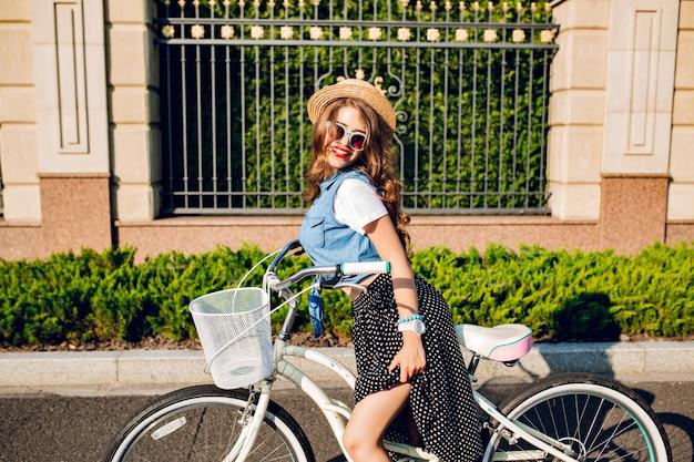 Hübsches mädchen mit langen lockigen haaren in der sonnenbrille posiert mit dem fahrrad auf der straße. sie trägt einen langen rock, ein wams, einen hut und rote lippen.