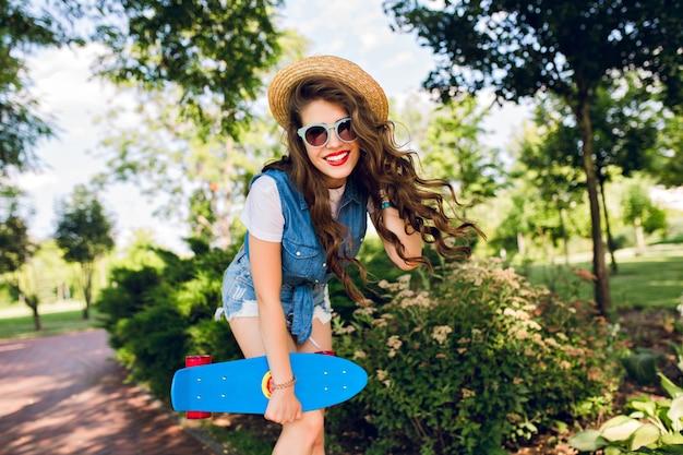 Hübsches mädchen mit langen lockigen haaren und roten lippen posiert mit skateboard im sommerpark. sie trägt jeanswams, sonnenbrille und hut.