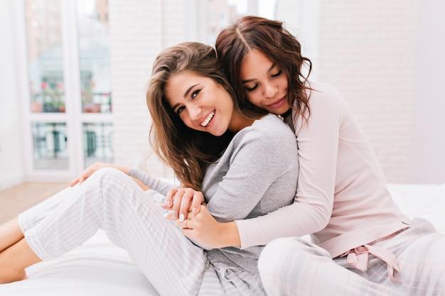 Hübsches mädchen mit lockigem haar umarmt von hinten lächelndes anderes mädchen. sie tragen einen pyjama.