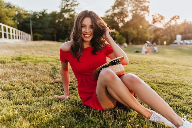 Hübsches mädchen mit schüchternem lächeln, das auf dem boden im park sitzt. gut gelaunte brünette frau im roten kleid, das am sonnigen tag auf dem gras aufwirft.