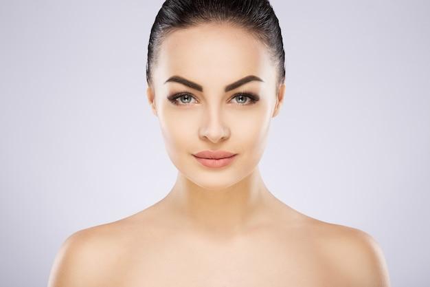 Hübsches mädchen mit schwarzen haaren, großen augen, dicken augenbrauen und nackten schultern in grau, ein modell mit hellem nacktem make-up, porträt, kopierraum.