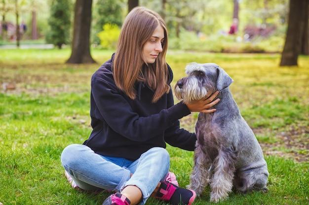 Hübsches mädchen mit seinem schnauzer-hund im naturpark im freien steht und posiert