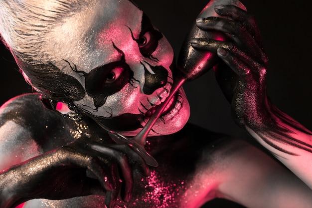 Hübsches mädchen mit skelett make-up hält glas