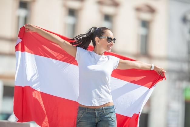 Hübsches mädchen mit sonnenbrille und weit geöffneten armen hält die österreichische flagge auf einer straße.