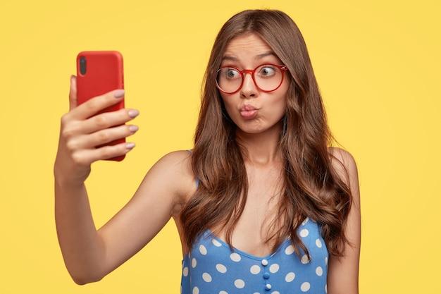 Hübsches mädchen nimmt selfie, schmollt lippen des handys, macht videoanruf, flirtet mit freund, schießt etwas für blog, macht foto von sich selbst, trägt brille, modelle gegen gelbe wand