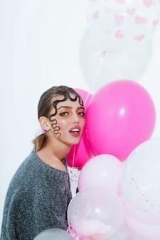 Hübsches mädchen oder schöne frau mit süßen lockigen blonden haaren, frisur und sexy rosigen lippen, stilvollem make-up, auf jungem gesicht mit partyballons, bunt, rosa, herzen auf weißem hintergrund