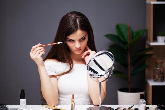 Hübsches mädchen trägt make-up auf gesicht zu hause nahe spiegel auf
