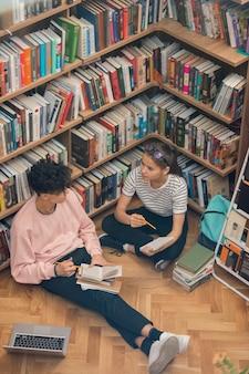 Hübsches mädchen und ihre klassenkameradin sitzen auf dem boden neben einem großen bücherregal in der universitätsbibliothek, während sie über die handlung eines romans sprechen