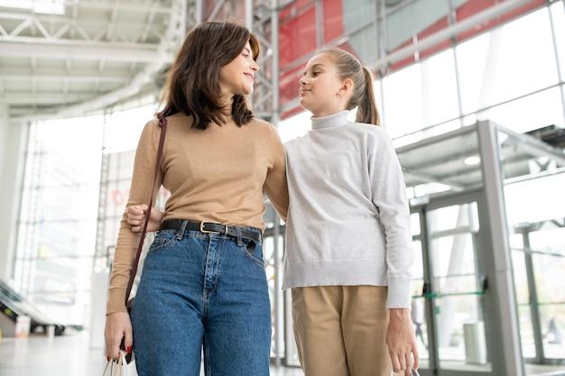 Hübsches mädchen und ihre mutter in umarmung schauen sich an, während sie das große einkaufszentrum hinuntergehen und sich unterhalten