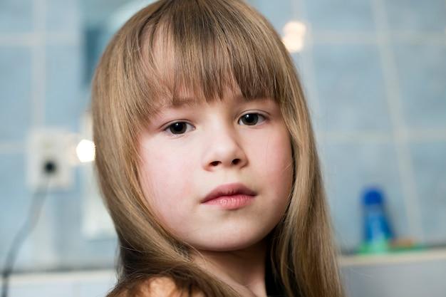 Hübsches mädchengesichtsporträt, kind mit schönen augen und langes nasses angemessenes haar auf unscharfem hintergrund des badezimmers.