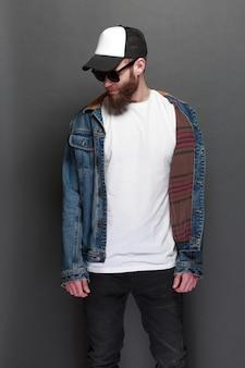 Hübsches männliches hipster-modell mit bart, das weißes leeres t-shirt und eine baseballkappe mit platz für ihr logo oder design im lässigen urbanen stil trägt