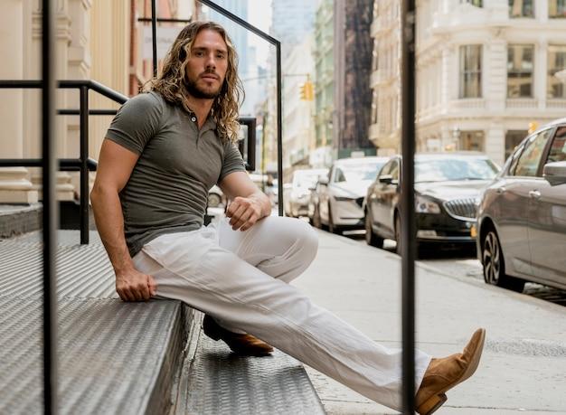 Hübsches männliches modell, das auf treppe aufwirft