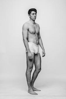 Hübsches männliches modell, das oben ohne auf dem weiß aufwirft