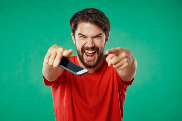 Hübsches männliches modell mit bart mit einem telefon, das aufwirft