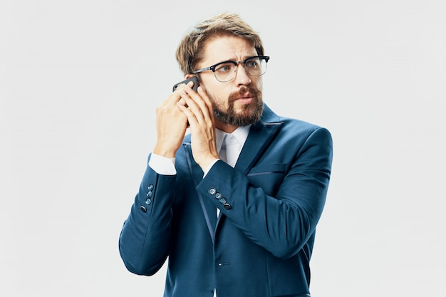 Hübsches männliches modell mit bart mit einem telefon, das im studio aufwirft