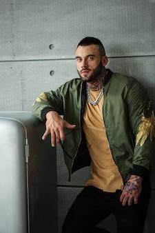 Hübsches männliches modell mit modetattoo und einem schwarzen bart, der in der nähe des stilvollen alten retro-kühlschranks der udssr in trendiger kleidung steht und posiert. professionelles studio-image.