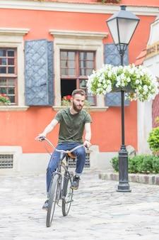 Hübsches männliches radfahrerreitenfahrrad auf pflasterung