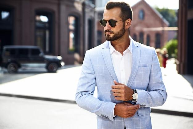 Hübsches modegeschäftsmannmodell gekleidet im eleganten blauen anzug, der auf straße aufwirft