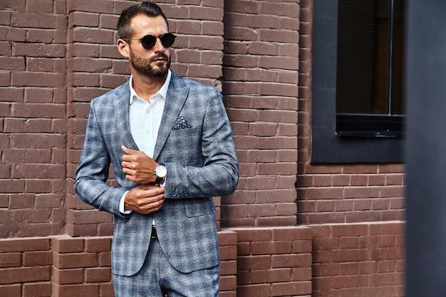 Hübsches modegeschäftsmannmodell gekleidet im eleganten karierten anzug, der auf straße aufwirft