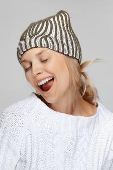 Hübsches model in weißem pullover und strickmütze, das mit weit geöffnetem mund lacht