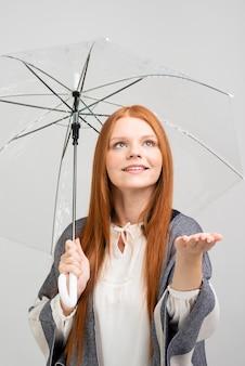 Hübsches modell des mittleren schusses, der regenschirm hält