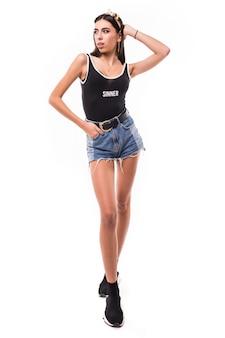 Hübsches modell langhaarige brünette frau in den kurzen blauen jeans und im schwarzen hemd lokalisiert