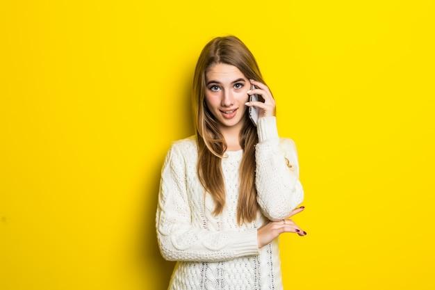 Hübsches modisches mädchen hat einen telefonanruf, der breiten weißen pullover auf gelb trägt