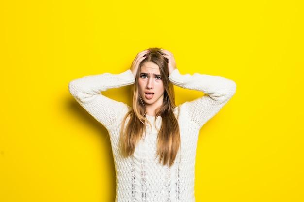 Hübsches modisches mädchen ist verwirrt, wenn es einen breiten weißen pullover auf gelb trägt