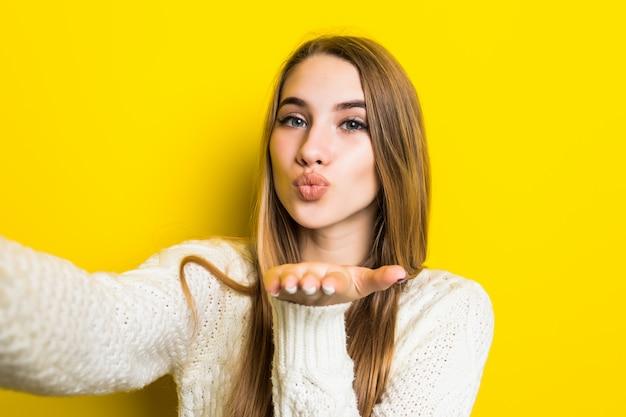 Hübsches modisches mädchen macht selfie-airkiss auf ihrem telefon und trägt einen breiten weißen pullover auf gelb
