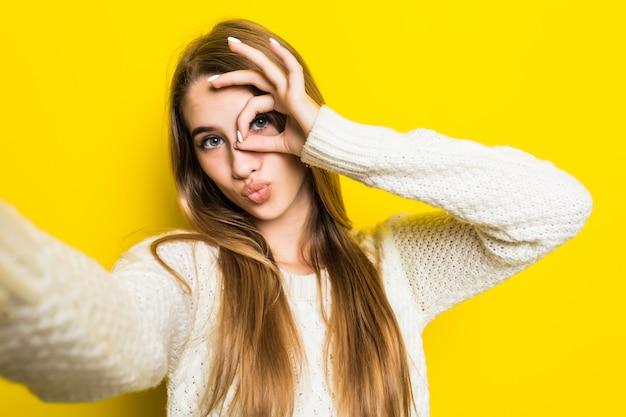 Hübsches modisches mädchen macht selfie auf ihrem telefon und trägt einen breiten weißen pullover auf gelb