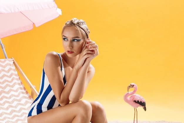 Hübsches modisches modell, das badeanzug auf sommerdekor trägt, das weg looing