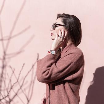 Hübsches modisches modemodell der jungen frau mit schönen langen haaren in stilvoller sonnenbrille in elegantem frühlingsmantel steht in der nähe der rosafarbenen wand und genießt helles sonnenlicht. schönes mädchen posiert im freien