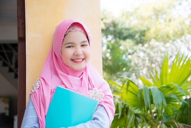 Hübsches moslemisches mädchen, das buch hält und in der schule lächelt.