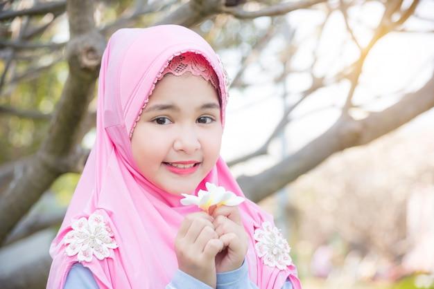 Hübsches moslemisches mädchen, das unter einem baum steht und weiße blume mit lächeln hält.