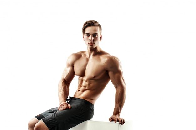 Hübsches muskulöses männliches modell, das auf einem würfel sitzt und über weißem hintergrund aufwirft.