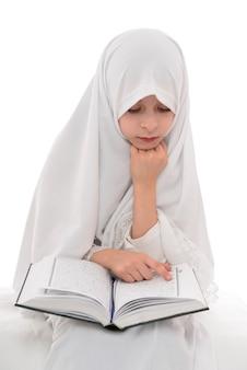Hübsches muslimisches mädchen, das heiliges buch des korans liest
