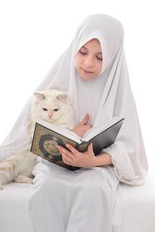 Hübsches muslimisches mädchen und katze mit heiligem buch des korans