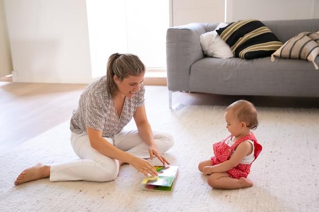 Hübsches mutter-lesebuch zum niedlichen kleinen baby in roten latzhose-shorts. konzentriertes kleinkind, das auf teppich im wohnzimmer sitzt und lesen lernt. familie, mutterschaft und zuhause sein konzept