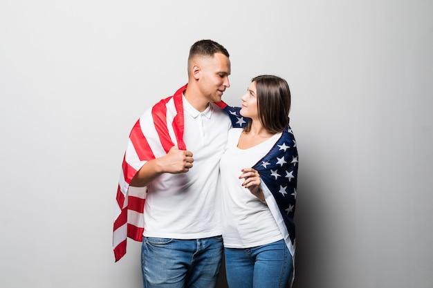 Hübsches paar hält us-flagge in den händen, bedeckt sich, während sie sich isoliert auf weiß beobachten