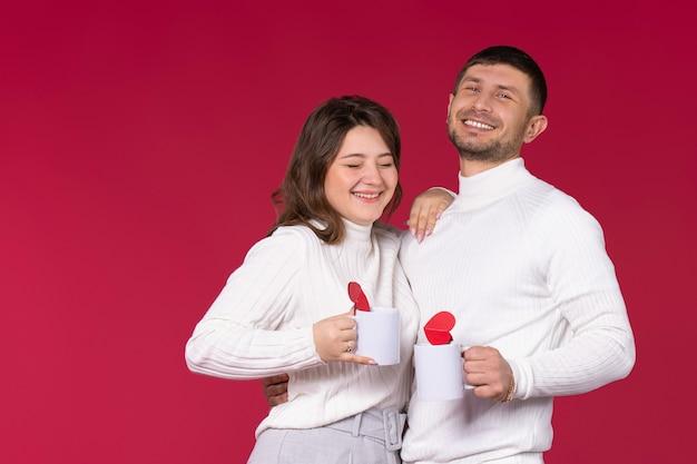Hübsches paar mit weißen tassen tee und herzen, die auf rotem hintergrund lachen.