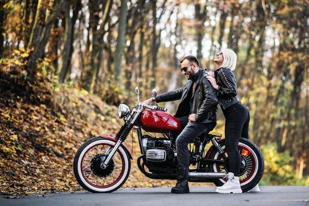 Hübsches paar nahe rotem motorrad auf der straße im wald