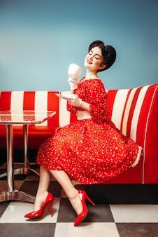 Hübsches pin-up-mädchen mit make-up trinkt kaffee im retro-café, 50 amerikanische mode. rotes kleid mit tupfen im vintage-stil
