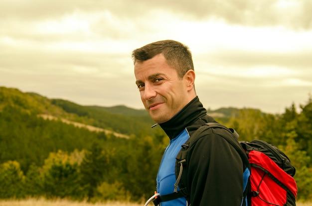 Hübsches porträt des jungen mannes an der gebirgsgrünlandschaft. porträt des erfolgreichen gesichtes des wanderers