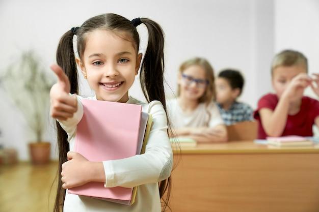 Hübsches, positives, cheerfuul schulmädchen, das in den handbüchern hält, daumen lächelt und sich zeigt.