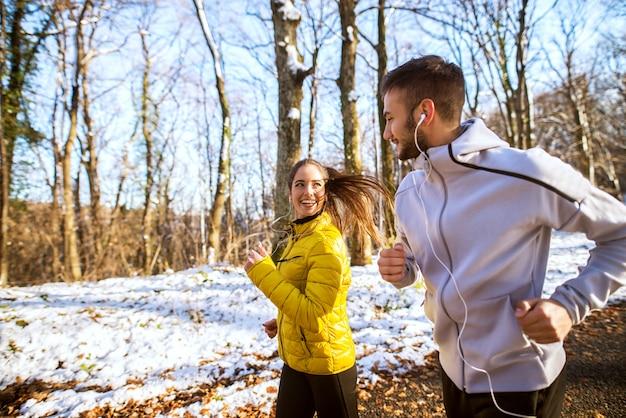 Hübsches reizendes junges gesundes paar, das mit kopfhörern und sportbekleidung durch den wald am wintermorgen läuft.