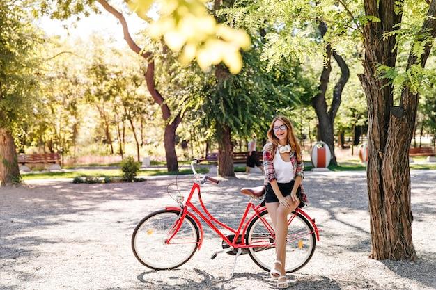 Hübsches schlankes mädchen, das auf rotem fahrrad sitzt. jocund stilvolle frau, die aktives wochenende genießt.