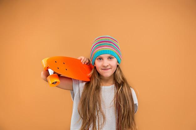 Hübsches schlittschuhläufermädchen, das skateboard hält