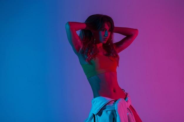 Hübsches schönes modemodell der jungen frau mit sexy körper in stilvoller kleidung glättet die haare im studio mit blauer farbe. modernes mädchen posiert in einem raum mit mehrfarbigem neonlicht-disco-stil.